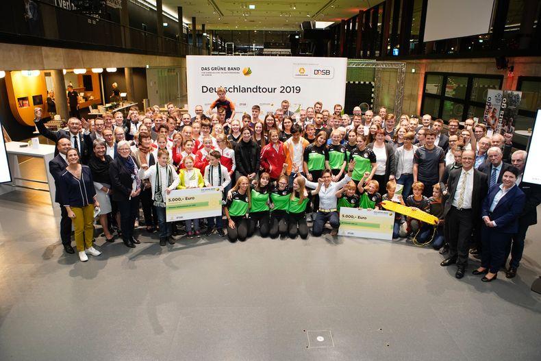 Foto: DOSB: Die ersten acht Preisträger des Grünen Bandes auf dem Gruppenfoto.