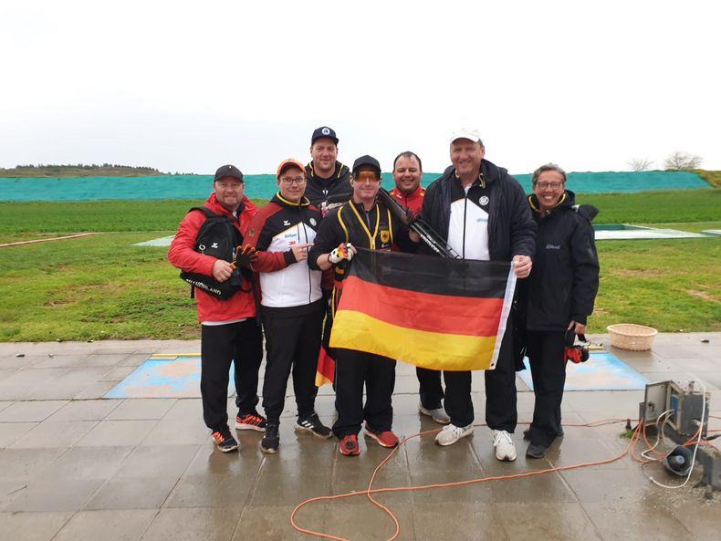 Foto: DSB / Bundestrainer Uwe Möller (2. v.r.) und die übrige deutsche Trap-Delegation beglückwünschen Andreas Löw.