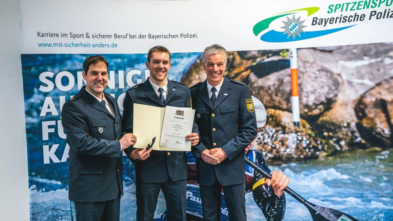Foto: Bayerische Polizei / Maximilian Dallinger (Mitte) bei der Urkundenübergabe zur Enennung zum Polizeimeister.