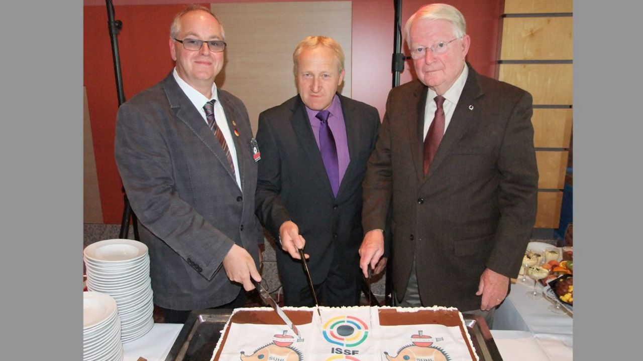 Foto: Michael Eisert / Zum 20-jährigen Jubiläum schnitten DSB-Vizepräsident Jugen Stefan Rinke, Willi Grill und Gary Anderson (beide ISSF) eine Torte an.
